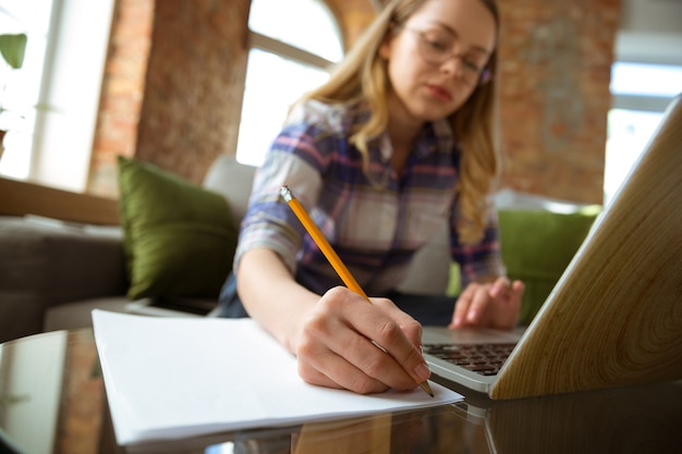 Młoda kobieta uczy się w domu podczas kursów online lub samodzielnie robi notatki