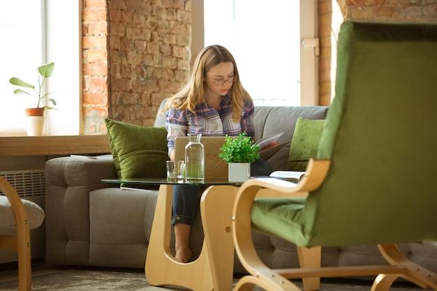 Młoda kobieta uczy się w domu podczas kursów online lub samodzielnie udziela bezpłatnych informacji, robi notatki