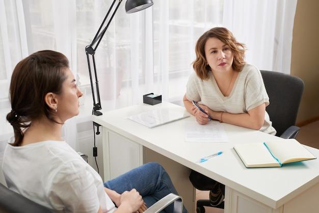Młoda kobieta uczy się z prywatnym nauczycielem przy stole, robienie notatek i czytanie