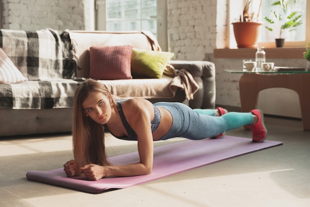 Młoda kobieta uczy w domu internetowych kursów fitness, aerobiku, sportowego stylu życia podczas kwarantanny. aktywność w izolacji, wellness, koncepcja ruchu. trening body, stretching, plank.