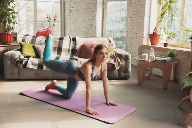 Młoda kobieta uczy w domu internetowych kursów fitness, aerobiku, sportowego stylu życia podczas kwarantanny. aktywność w izolacji, wellness, koncepcja ruchu. trening dolnej części ciała, stretching.