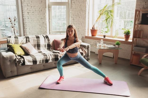 Młoda kobieta uczy w domu internetowych kursów fitness