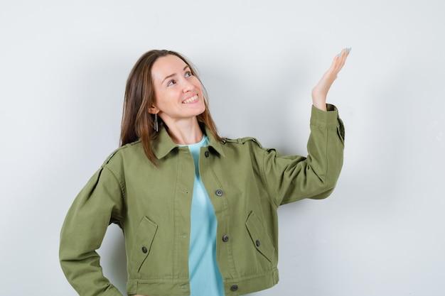 Młoda kobieta udając, że pokazuje coś, patrząc w górę w zielonej kurtce i patrząc jowialnie. przedni widok.