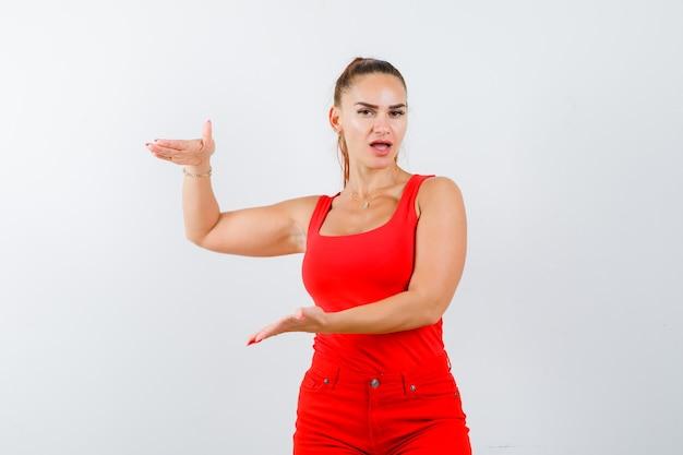 Młoda kobieta, udając, że trzyma coś w czerwonym podkoszulku, spodniach i patrząc zamyślony, widok z przodu.