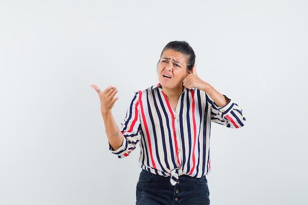 Młoda kobieta udająca rozmowę przez telefon w bluzce w paski i wyglądająca na zaciekawioną.