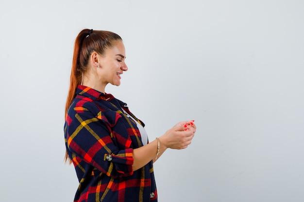 Młoda kobieta udaje, że trzyma coś w kraciastej koszuli i wygląda na szczęśliwą. przedni widok.