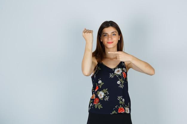 Młoda kobieta udaje, że wskazuje na zegarek na jej nadgarstku w bluzce, spódnicy i wygląda wesoło, widok z przodu.