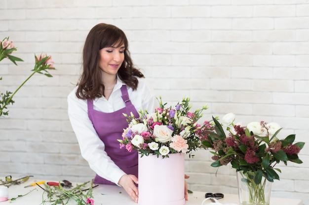 Młoda kobieta układa piękny bukiet w kwiaciarni.
