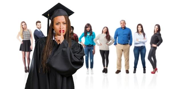 Młoda kobieta ukończył czarny noszenie warkoczy, trzymając w tajemnicy lub prosząc o ciszę