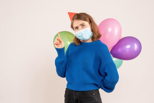 Młoda kobieta ukrywa kolorowe balony za plecami na białym tle