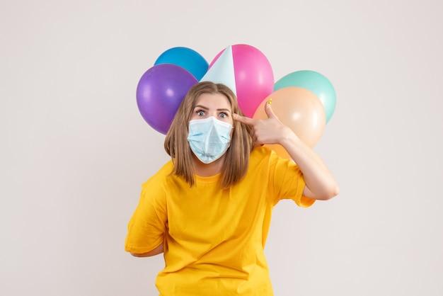 Młoda kobieta ukrywa kolorowe balony za plecami w masce na białym tle