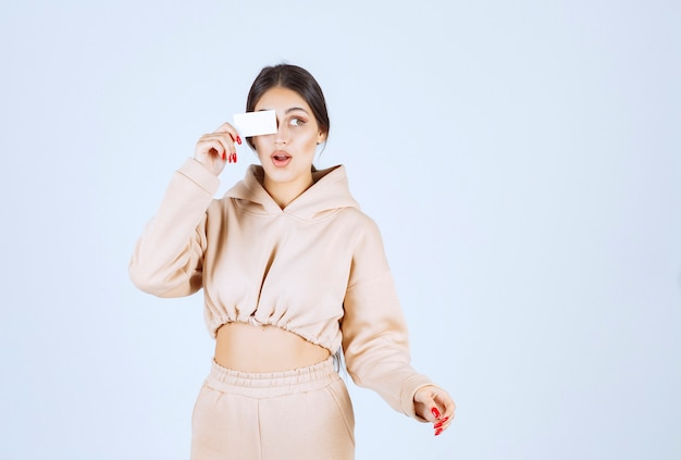 Młoda kobieta umieszczenie wizytówki na jej oko