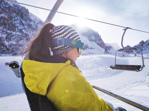 Młoda kobieta unosi się na wyciągu krzesełkowym. wyciąg narciarski pod błękitnym niebem na tle skały.