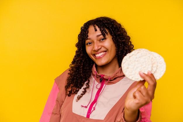 Młoda kobieta uprawiająca sport mieszany, jedząca ciastka ryżowe odizolowane na żółto