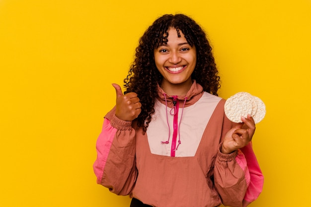 Młoda kobieta uprawiająca sport mieszany, trzymająca ciastka ryżowe na żółto, uśmiechnięta i unosząca kciuk w górę