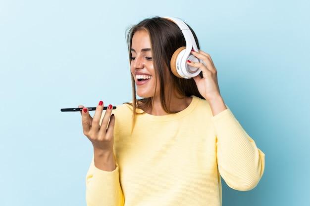 Młoda kobieta urugwaju samodzielnie na niebiesko słuchania muzyki z telefonu komórkowego i śpiewu