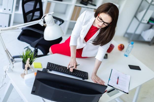 Młoda kobieta usiadła na biurku w biurze i pracuje z dokumentami i komputerem.