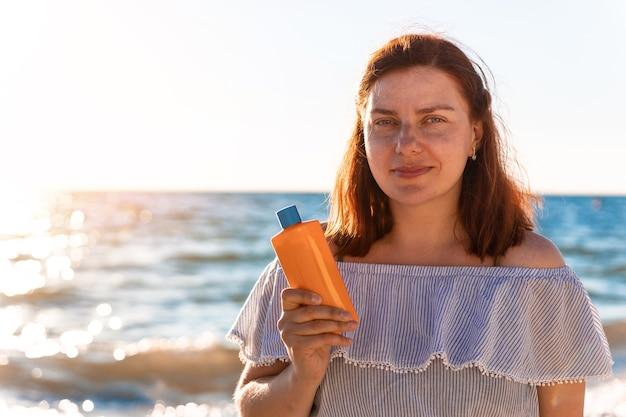 Młoda kobieta uśmiech z butelką kremu przeciwsłonecznego krem przeciwsłoneczny uv chroni na plaży w pobliżu morza o świcie. ochrona i pielęgnacja skóry