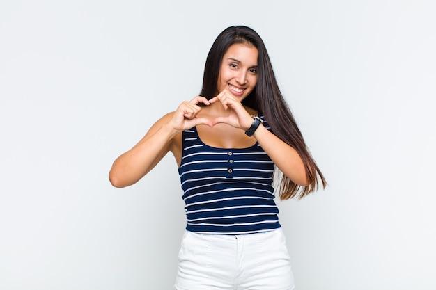 Młoda kobieta uśmiecha się i czuje się szczęśliwa, słodka, romantyczna i zakochana, tworząc kształt serca obiema rękami