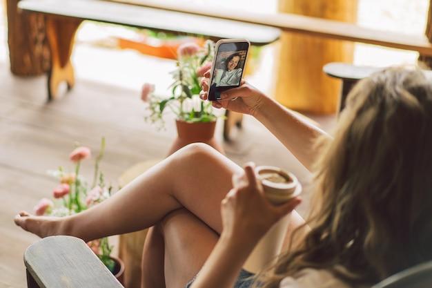 Młoda kobieta uśmiecha się i patrzy w kamerę i przyjmuje koncepcję stylu życia selfie