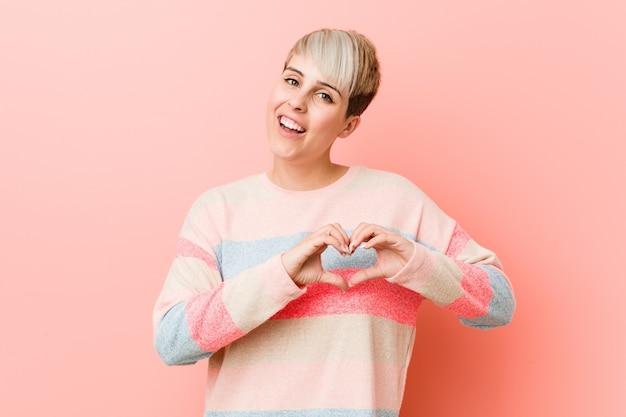 Młoda kobieta uśmiecha się i pokazuje kształt serca rękami