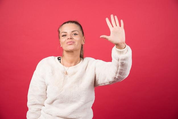 Młoda kobieta uśmiecha się i pokazuje numer pięć palcami
