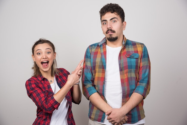 Młoda kobieta uśmiecha się i wskazuje na obrażonego mężczyznę.