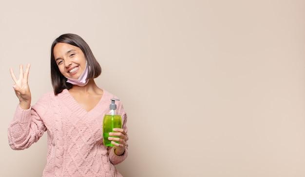 Młoda kobieta uśmiecha się i wygląda przyjaźnie, pokazując numer trzy lub trzeci z ręką do przodu, odliczając