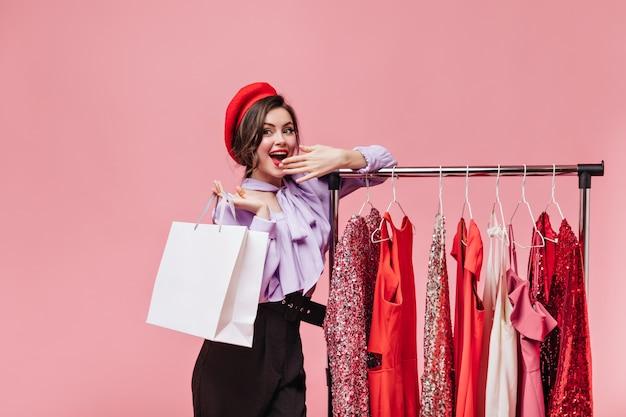 Młoda kobieta uśmiecha się i zakrywa usta podczas zakupów. dama w berecie pozuje obok stojaka z fantazyjnymi sukienkami.