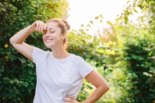 Młoda kobieta uśmiecha się na zewnątrz. piękna brunete dziewczyna na zielonym tle park lub ogród. wolna szczęśliwa kobieta w okresie letnim. wolność szczęście beztroski koncepcja szczęśliwych ludzi.
