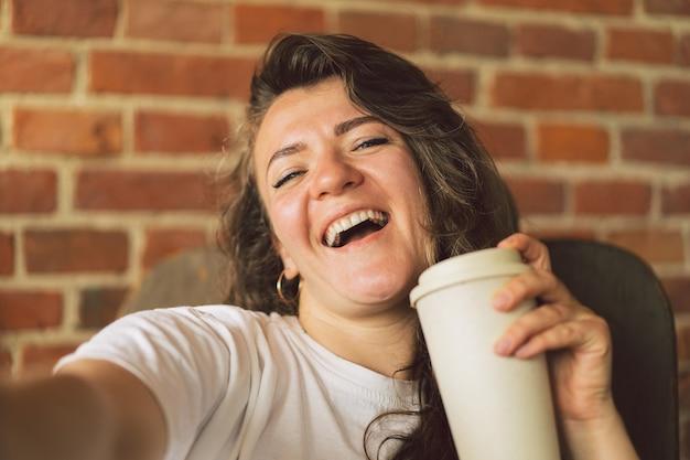 Młoda kobieta uśmiecha się pijąc kawę i patrząc w kamerę i przyjmuje koncepcję stylu życia selfie
