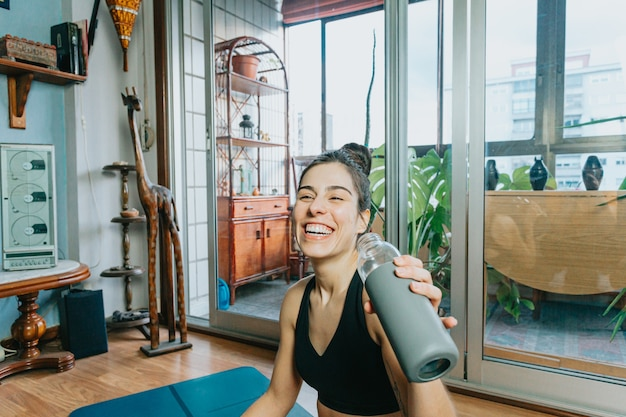 Młoda kobieta uśmiecha się podczas picia wody robi fitness i jogi w domu