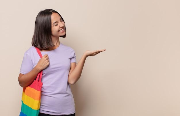 Młoda kobieta uśmiecha się radośnie, czuje się szczęśliwa i pokazuje koncepcję w przestrzeni kopii z dłonią