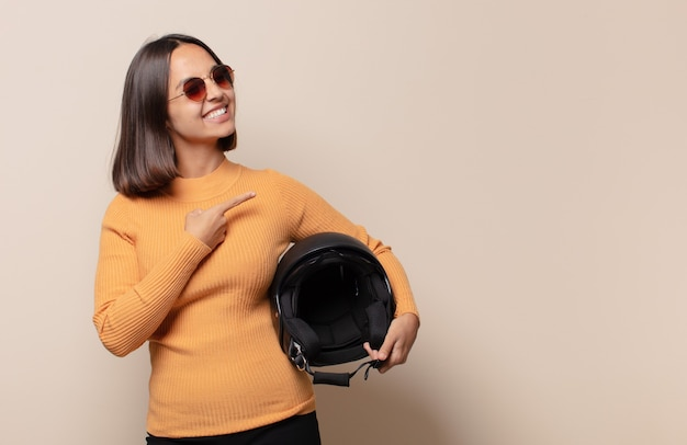 Młoda kobieta uśmiecha się radośnie, czuje się szczęśliwa i wskazuje na bok i do góry, pokazując obiekt w przestrzeni kopii
