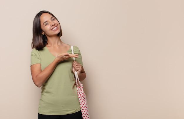 Młoda kobieta uśmiecha się radośnie, czuje się szczęśliwy i pokazuje koncepcję w przestrzeni kopii z dłoni