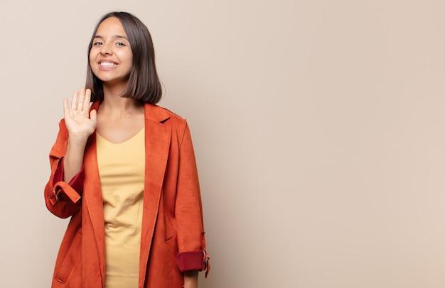 Młoda kobieta uśmiecha się radośnie i wesoło, macha ręką, wita i wita lub żegna się