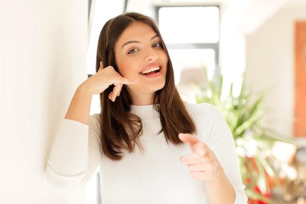 Młoda kobieta uśmiecha się radośnie i wskazuje na aparat podczas wykonywania połączenia później gest rozmawia przez telefon