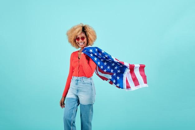 Młoda kobieta uśmiecha się trzymając flagę usa na na białym tle. koncepcja obchodów dnia niepodległości.