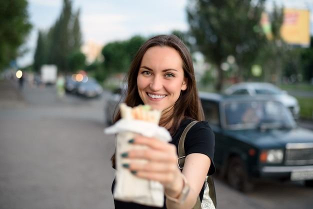 Młoda kobieta uśmiecha się, trzymając shawarmę owiniętą w lawasz