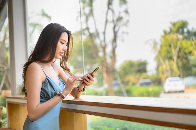 Młoda kobieta uśmiecha się z szczęśliwą ręką naciskając smartphone