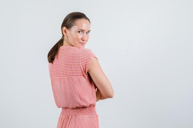 Młoda kobieta uśmiecha się ze skrzyżowanymi rękami w pasiastej sukience, widok z tyłu.