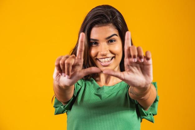 Młoda kobieta uśmiechając się, co ramka na zdjęcia z rąk i palców z szczęśliwą twarzą. koncepcja kreatywności i fotografii.