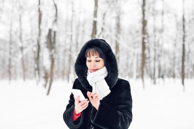 Młoda kobieta uśmiechając się z inteligentnego telefonu i zimowy krajobraz i płatki śniegu na tle.