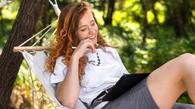 Młoda kobieta uśmiechnięta, leżąc na hamaku i za pomocą tabletu z rysikiem. wokół zieleń. glamping