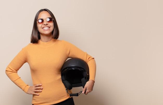 Młoda kobieta uśmiechnięta radośnie z ręką na biodrze i pewną siebie, pozytywną, dumną i przyjazną postawą