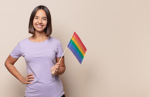 Młoda kobieta uśmiechnięta radośnie z ręką na biodrze i pewna siebie, pozytywna, dumna i przyjazna