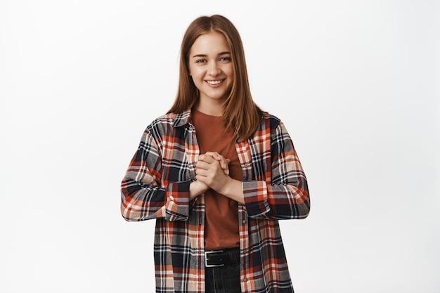 Młoda kobieta uśmiechnięta trzymająca się za ręce zaciśnięta w pobliżu klatki piersiowej pełna nadziei, prosząca o coś, mająca nadzieję, błagająca o szansę, stojąca przy białej ścianie