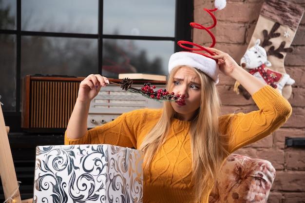 Młoda kobieta ustala jej kapelusz santa i patrząc na holly jagody.