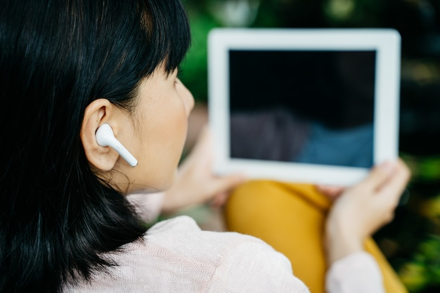 Młoda kobieta używa bezprzewodową słuchawkę i pastylkę