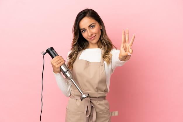 Młoda kobieta używa blendera ręcznego na izolowanym różowym tle szczęśliwa i liczy trzy palcami